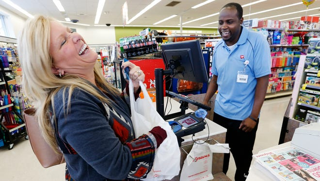 Pattie Bunch laughs as she is helped by cashier Dwayne Cordner at the Walgreens on Freemont Avenue and Republic Road.