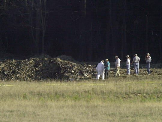 Officials examine the crater at the crash site of United Airlines Flight 93 in Shanksville, Pennsylvania on Sept. 11, 2001.