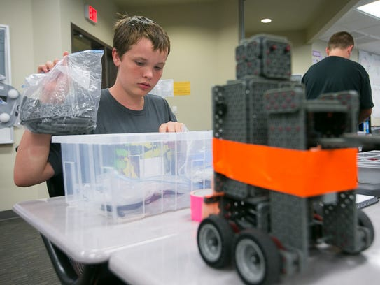 Student Bradey Black, 12, works on a robot during class