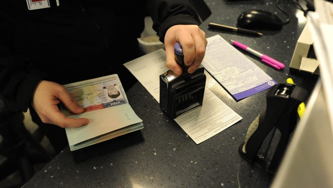 In this file photo from Feb. 23, 2012, U.S. Customs agent Rebecca O'Neill stamps the visa of a non-U.S. citizen at the inspection area of Washington Dulles International Airport.