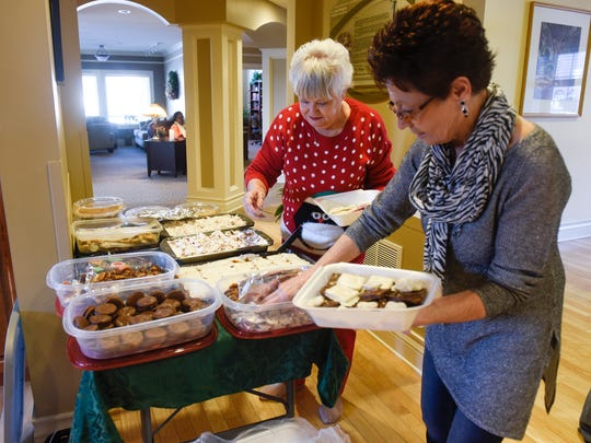 Pat Peterson and Ione Reynolds make to-go boxes with sweet treats at the Gorecki Guest House Monday, Dec. 25, in St. Cloud.