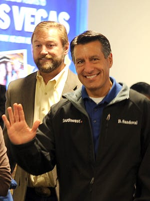 Nev. Gov. Brian Sandoval, waves to well-wishers at the Reno Tahoe International Airport Friday Oct. 31, 2014 to celebrate the state's 150th birthday. Behind him is Nev. U.S. Sen. Dean Heller.