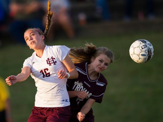 Henderson County's Katie Bickers (16) heads the ball