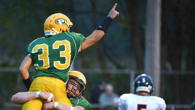 Pennfield running back Michael Davis (33) celebrates a touchdown on Friday.