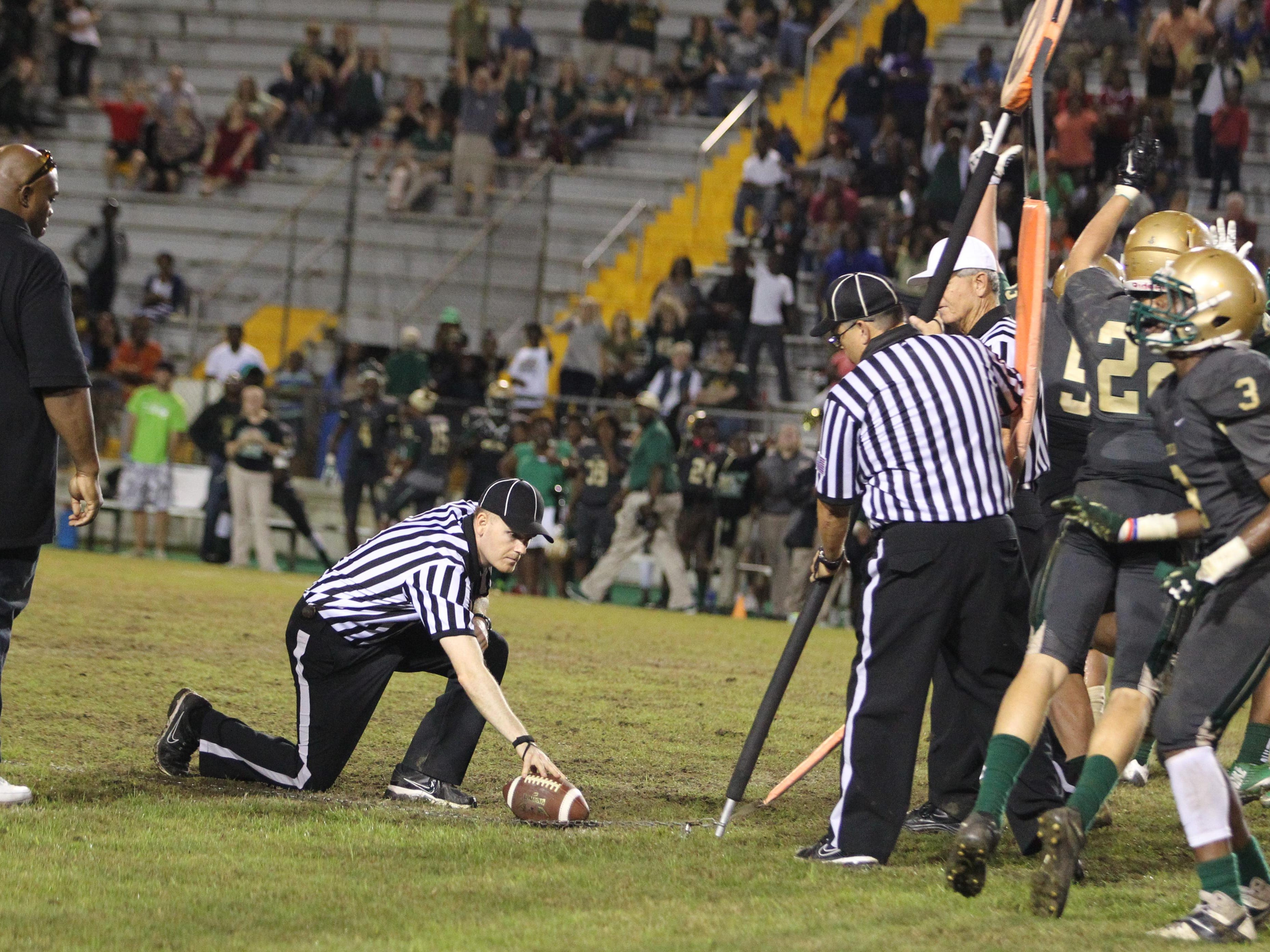 Lincoln players react as referees decide a fourth-quarter play didn't give Godby enough yards for a first down, effectively ending the game with a few seconds left on the clock. As a result, Lincoln beat Godby 42-34 when the Cougars' final drive stalled.