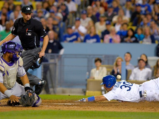 Los Angeles Dodgers' Darwin Barney, right, scores on a single by Scott Van Slyke as the ball gets by Colorado Rockies catcher Wilin Rosario, left, while home plate umpire Jim Reynolds watches during the sixth inning of a baseball game, Friday, Sept. 26, 2014, in Los Angeles. (AP Photo/Mark J. Terrill)