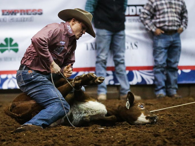 Tuf Cooper ties down a calf during the 6th performance