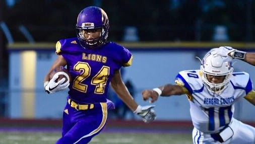 Ozona running back Zachary Talamantez (24) breaks away from a Reagan County defender during the Lions' 29-16 win over the Owls in Ozona on Friday, Sept. 29, 2017.