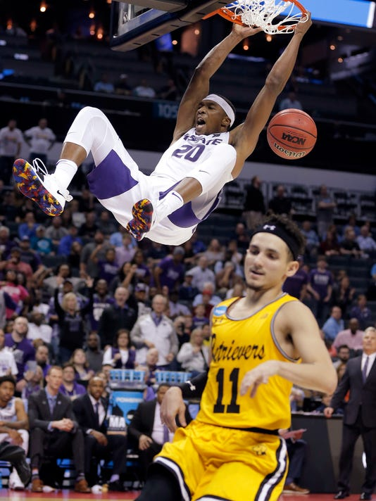 Kansas State's Xavier Sneed (20) dunks as UMBC's K.J. Maura (11) runs past during the second half of a second-round game in the NCAA men's college basketball tournament in Charlotte, N.C., Sunday, March 18, 2018. (AP Photo/Bob Leverone)