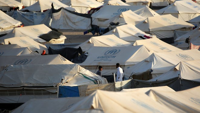 Men stand in between  tents at a United Nations refugee camp housing Iraqi families who fled fighting in the Mosul area on Oct. 17, 2016, in the northeastern town of al-Hol in Syria's Hasakeh province.  The battle to retake the Iraqi city of Mosul from the Islamic State could unleash a massive humanitarian crisis.