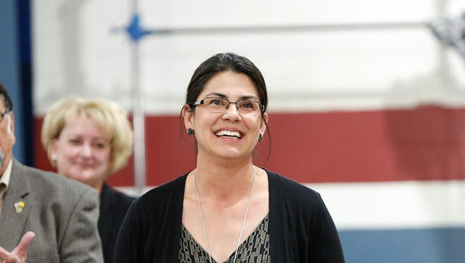 Math teacher and Western New Mexico University alumna Melanie Alfaro (pictured center) accepts New Mexico's 2017-18 Milken Educator Award and listens to applause at the surprise awards assembly at Deming Intermediate School last month.