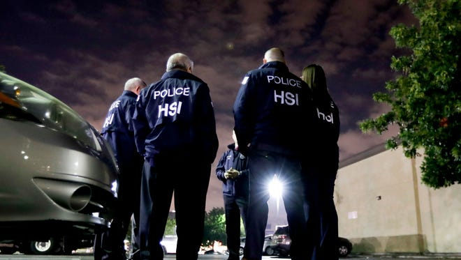 U.S. Immigration and Customs Enforcement agents gather before serving a employment audit notice at a 7-Eleven convenience store Wednesday, Jan. 10, 2018, in Los Angeles.