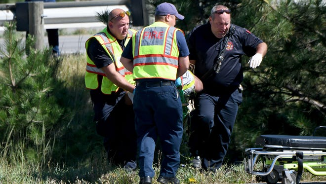 Rescuers carry a man out of a ravine on the U.S. 30 exit at U.S. 42 Tuesday afternoon.