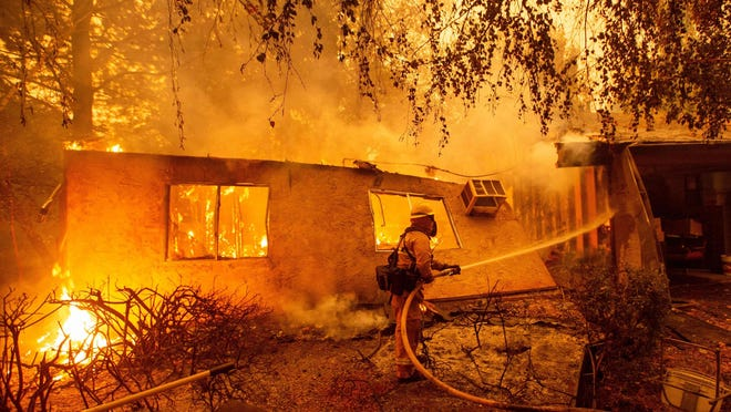 Firefighters battle flames at a burning apartment complex in Paradise, north of Sacramento, on Nov. 9. 2018.