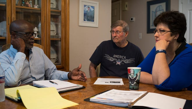 Mary Kay Hoskovec and her husband, Gene Hoskovec (center) talk with financial planner Fola Odejimi in their Glendale home.
