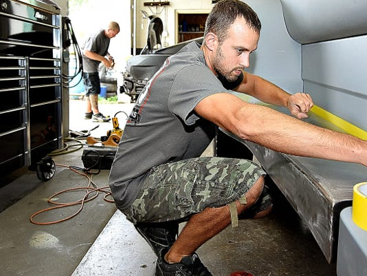 Travis Coryman, front, tapes off an area to begin work on a running board Wednesday while Glenn Michael, back, uses tape as he prepares to make a mold for a spoiler at Legacy Innovations on Andrews Street in West York. The custom car shop will be moving to a much larger space in Manchester Township soon, owner Troy Spackman said.