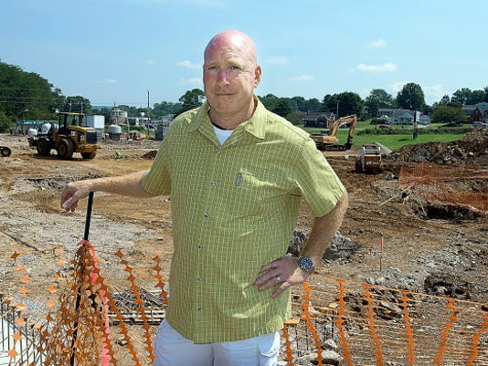 Leg Up Farmers Market Chief Operating Officer Brad Clark stands near a construction fence Monday as excavation continues on the locally sourced grocery store in progress. The market is slated to open in February at the former site of Brown's North.