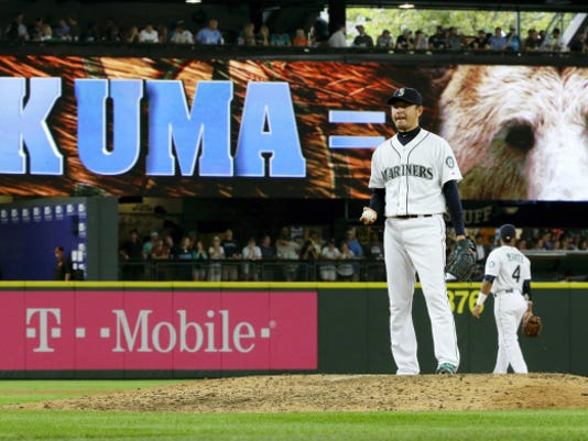 """Seattle starting pitcher Hisashi Iwakuma stands on the mound in the eighth inning of his no-hitter against the Baltimore Orioles, in front of an electronic sign that reads """"Kuma ="""" and shows a photo of a bear, during Wednesday's game in Seattle. The Japanese word """"kuma"""" means """"bear"""" in English. The Mariners won, 3-0."""