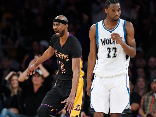 Los Angeles Lakers forward Corey Brewer, left, celebrates after scoring as Minnesota Timberwolves forward Andrew Wiggins stands nearby during the second half of an NBA basketball game, Friday, March 24, 2017, in Los Angeles. The Lakers won 130-119 in overtime. (AP Photo/Mark J. Terrill)