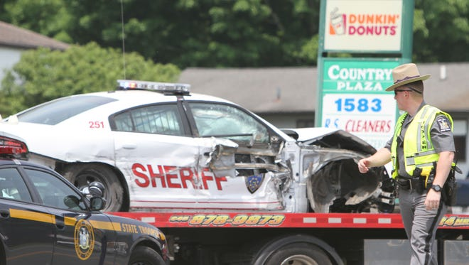 A state trooper watches as a Putnam County Sheriff's vehicle is removed from the scene of an accident on Route 22 in the town of Southeast May 29, 2016. The deputy was in pursuit of a speeding motorcycle when his vehicle struck a utility pole in front of 1583 Route 22. The deputy was uninjured, and the motorcycle was able to get away.