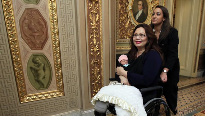 Sen. Tammy Duckworth, D-Ill., with her baby Maile leaves the Senate floor after voting on Capitol Hill.