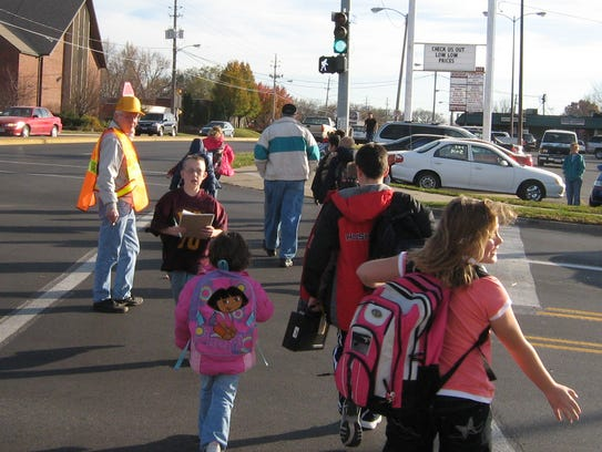 Crossing guard Joe Wray, 63, helps students from Park