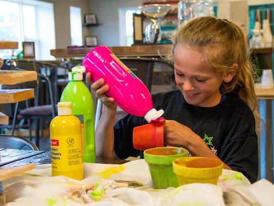 MéShelle's 11-year-old daughter, Elsa, paints a flower