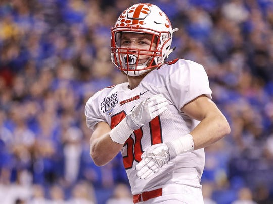 Center Grove TrojansÕ Titus McCoy (30) celebrates after making his way into the end zone against Carmel in the Class 6A state title game at Lucas Oil Stadium on Friday, Nov. 25, 2016.