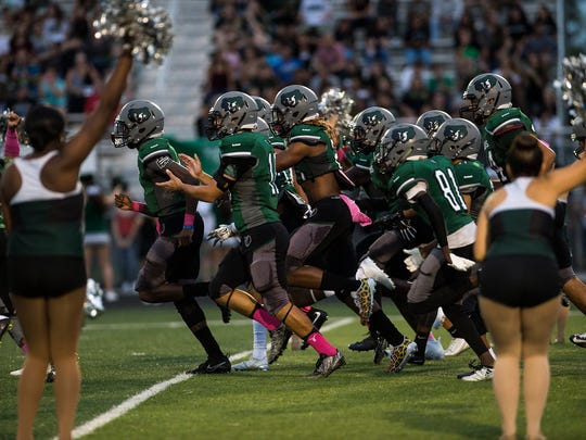 Palmetto Ridge High School's football team takes to the field before a game against Immokalee High School last year.