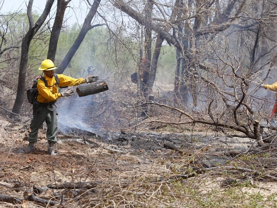 Firefighters continued removing material and extinguishing hot spots on Monday after 100 acres was burned the day before in the Mesa Farm area in Shiprock.