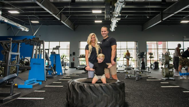 Kate and David Champlin, owners of Battle Ground Fitness, pose for a portrait with their son Jackson inside their new gym facility on October 10, 2017.