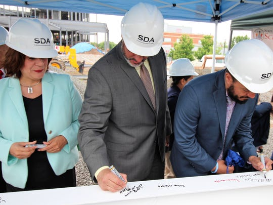 Officials, including Perth Amboy Mayor Wilda Diaz, sign a beam for the new Seaman Avenue Elementary School in Perth Amboy.