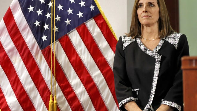 U.S. Rep. Martha McSally, R-Ariz., waits to speak during a news conference Tuesday, Dec. 18, 2018, at the Capitol in Phoenix, where Arizona Gov. Doug Ducey, rear, announced his decision to replace U.S. Sen. Jon Kyl, R-Ariz. with McSally in the U.S. Senate seat that belonged to Sen. John McCain. McSally will take over after Kyl's resignation becomes effective Dec. 31.