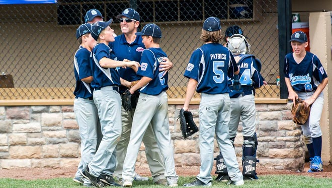 Coach Sean McGrath celebrates with his South Burlington team after the fifth inning.