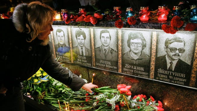 Ukrainians light candles and lay flowers at a memorial in Slavutich for 'liquidators' who died during clean up operations after the Chernobyl nuclear power plant disaster on April, 26, 1986.