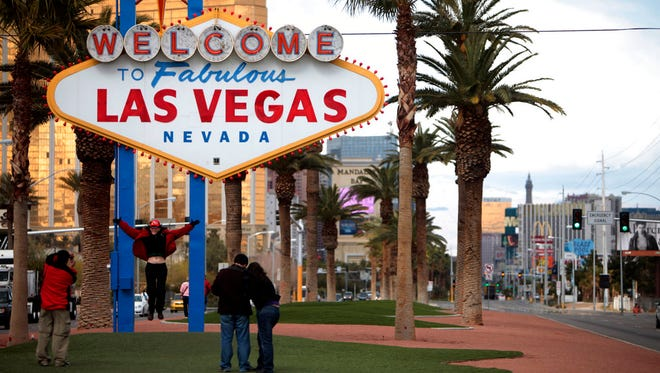 "In this Feb. 12, 2009, file photo, tourists take pictures in front of the Las Vegas welcome sign. The official slogan of Las Vegas, ""What happens here, stays here,"" is back by popular demand. The destination's tourism agency revived the 15-year-old slogan this week, three months after it was put on hold following the October mass shooting."