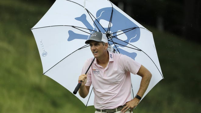 Brendon Todd looks at a competitors tee shot while sheltering from the rain with an umbrella on the 18th hole during the third round of the Travelers Championship golf tournament at TPC River Highlands on Saturday in Cromwell, Conn.