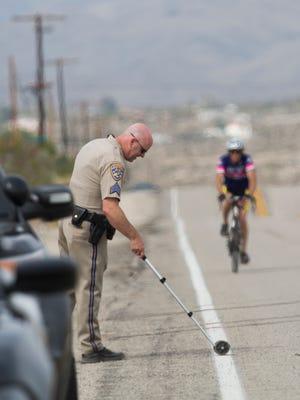 Two cyclists participating in the 2018 Tour de Palm Springs were struck by a vehicle speeding on Dillon Road near the intersection with 30th Avenue. One of the cyclists was pronounced dead at the seen while the other cyclist was airlifted to Desert Regional Hospital in Palm Springs, California on February 10, 2018. The driver was also taken to Desert Regional Hospital via ambulance. In this photo a California Highway Patrol officer conducts an investigation as a cyclist passes the seen of the fatality.