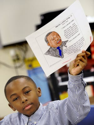 Evan Bowman shows a picture of Martin Luther King Jr. he colored at last year's MLK Day of Service at Bellingrath Middle School.