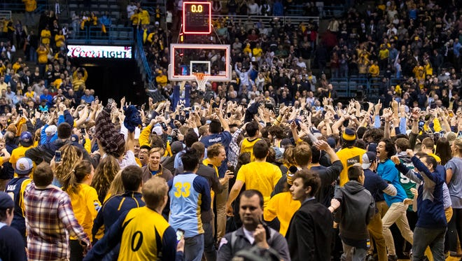 Marquette fans storm the court after the team's upset victory over top-ranked Villanova Tuesday night.