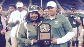 Detroit Cass Tech coach Thomas Wilcher poses with the PSL title trophy Friday at Ford Field.
