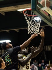 UMFK Benson Arogbo tries to block a layup from UVM's Samuel Dingba who sank the attempt during their men's basketball match up at Patrick Gym on Wednesday night, Nov. 22, 2017.