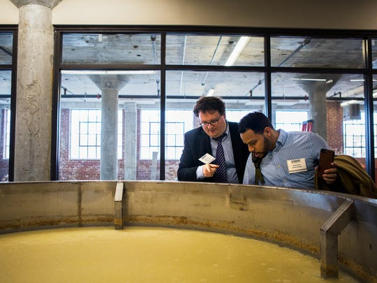 Brett Roler (left), vice president of planning and development, and Chris Porter, creative manager, both gentlemen with the Downtown Memphis Commission, look at the process of alcoholic fermentation during a tour of the new Old Dominick distillery at 305 S. Front on Thursday, Jan. 27, 2017.