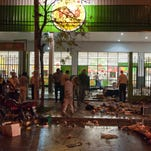 An armed guard look at  items left behind by looters after the supermarket was looted in San Miguel de Tucuman, Argentina, Monday.