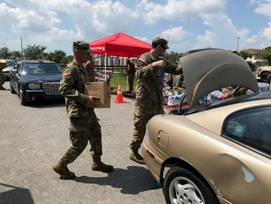 National Guard members help load a car with food and
