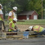 A crew installs curbing along Salisbury Road in front of the Wayne County Fairgrounds.