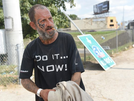 Pete Bello holds his sign as he panhandles along I-75