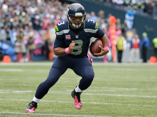 Seattle Seahawks quarterback Russell Wilson (3) runs for a touchdown in the second half of an NFL football game against the Dallas Cowboys, Sunday, Oct. 12, 2014, in Seattle. (AP Photo/Elaine Thompson)