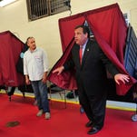 Election worker Norberto Rivera watches as Gov. Chris Christie emerges from the voting booth at Mendham Township's Emergency Services Building Tuesday evening.Photos by Karen Macinelli/Staff photographer