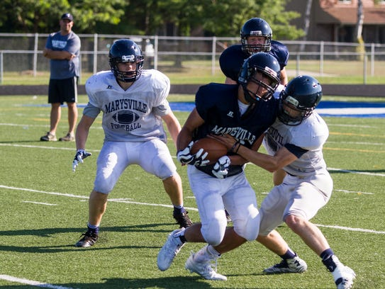 Marysville High School players run drills during a